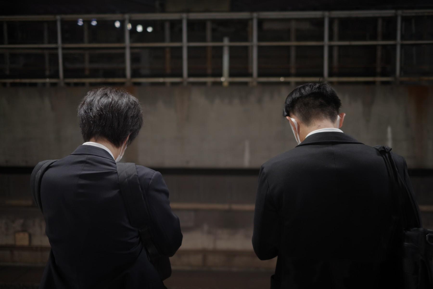 駅のホームに並ぶ会社帰りのサラリーマンの作例写真