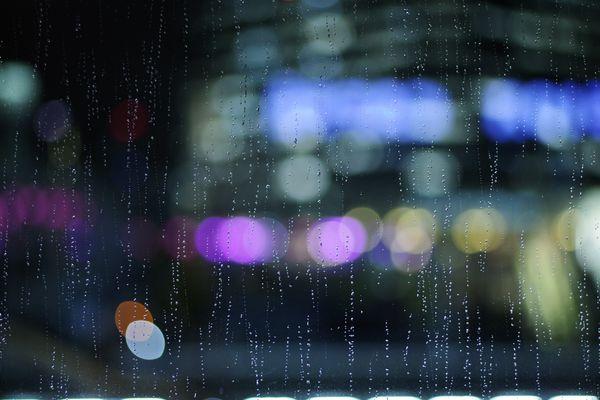 ガラスに滴る雨と夜の街の作例写真