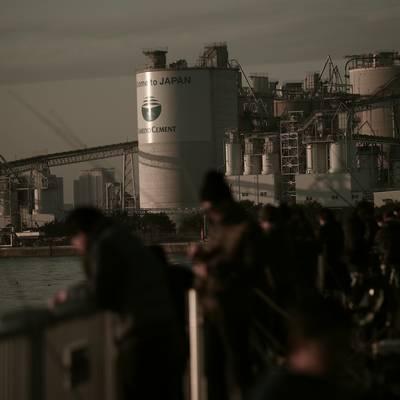 若洲海浜公園の防波堤で釣りをする人々とセメント工場の作例写真