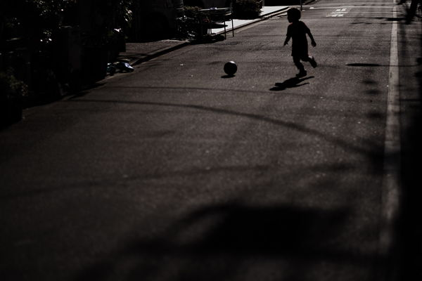 路上でボール遊びをする子供の作例写真