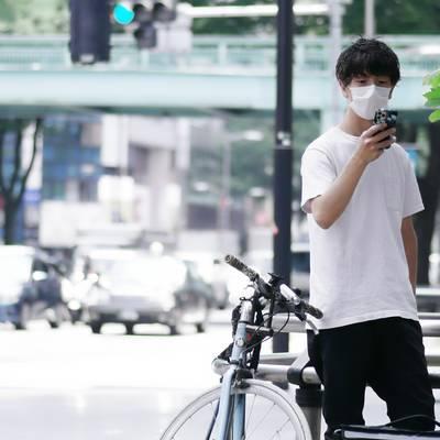 スマホを確認する自転車配達員の作例写真